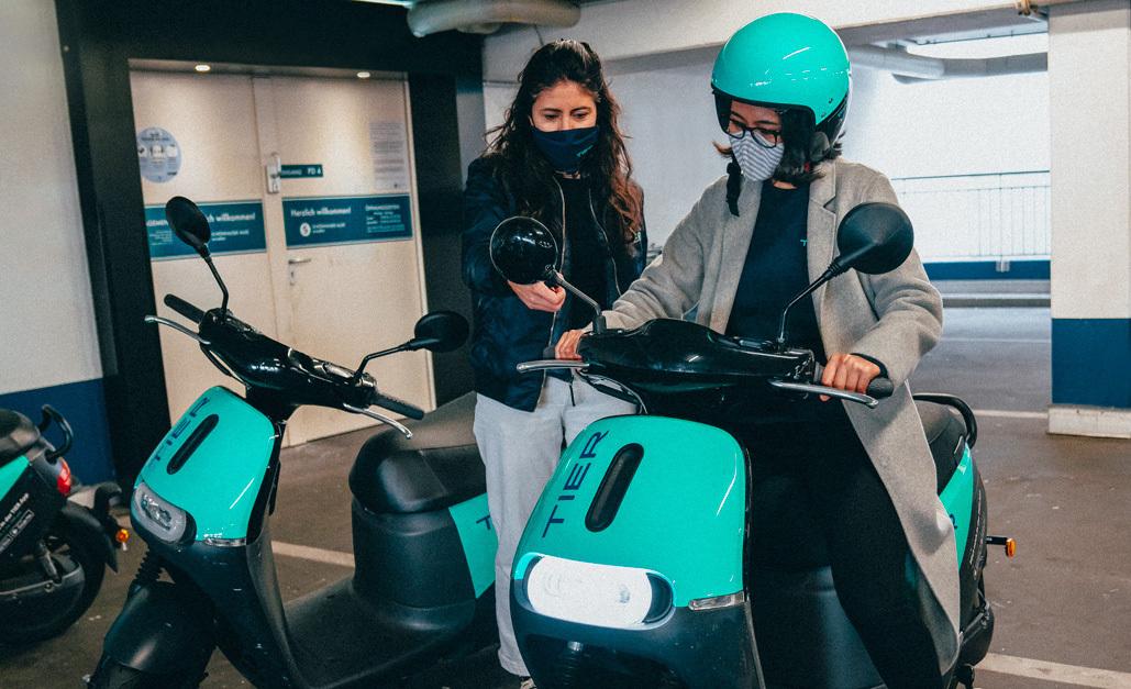 Eine Frau zeigt einer anderen Frau ein E-Moped