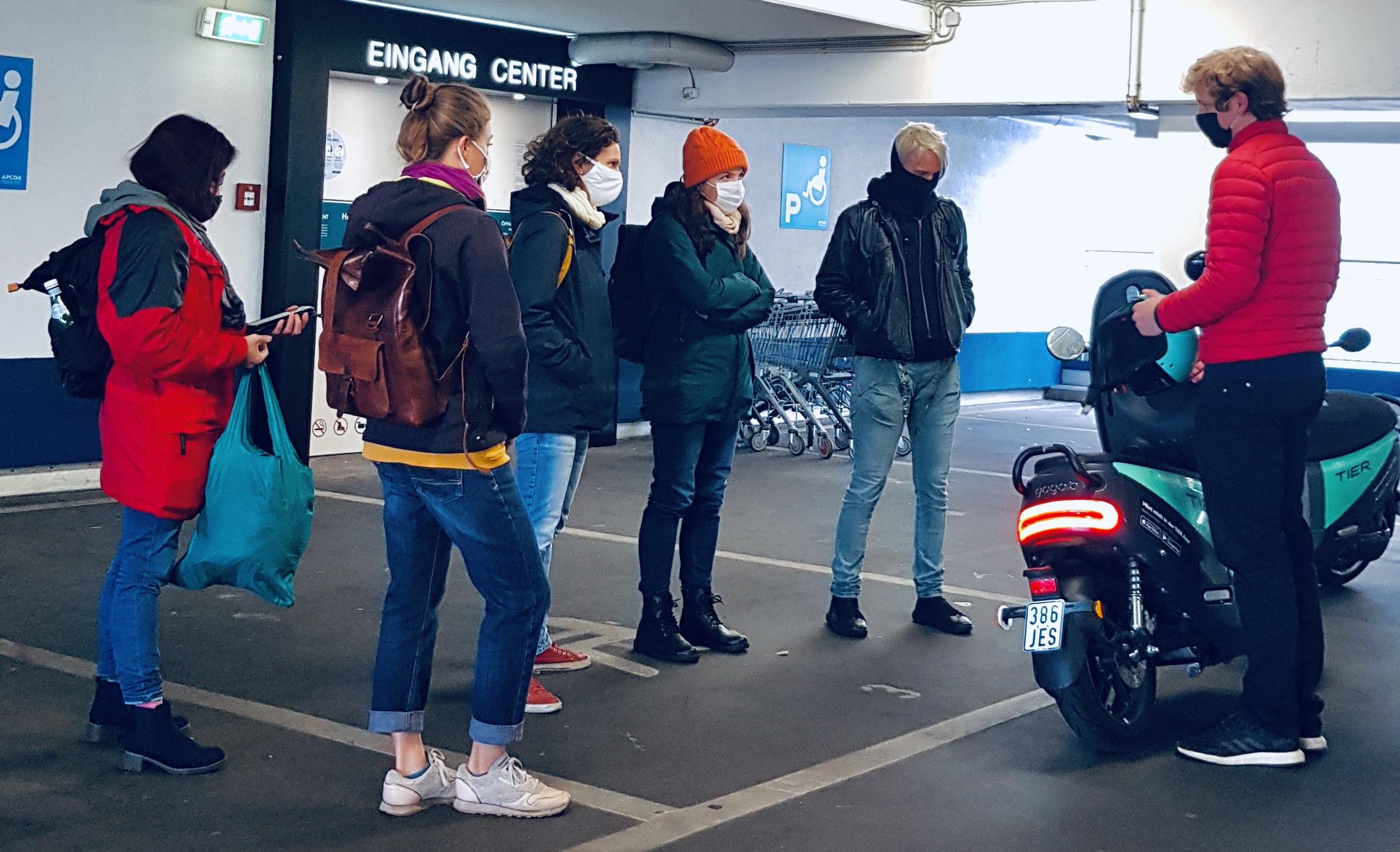 Eine Person erklärt einer Gruppe von Frauen die Nutzung eines E-Mopeds